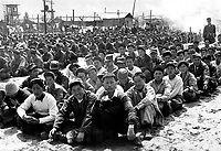 At the United Nations' prisoner-of-war camp at Pusan, prisoners are assembled in one of the camp compounds.  The camp contains both North Korean and Chinese Communist prisoners.  April 1951.  Gahn, State Dept.  (USIA)<br /> Exact Date Shot Unknown<br /> NARA FILE #:  306-PS-51-7134<br /> WAR & CONFLICT BOOK #:  1496
