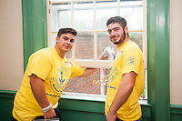 Anthony Morico,'20  and Angelo Disanto,'20, wash windows at the Seamen's Church Institute as part of Salve Regina's Exploration Day of Service in Newport.
