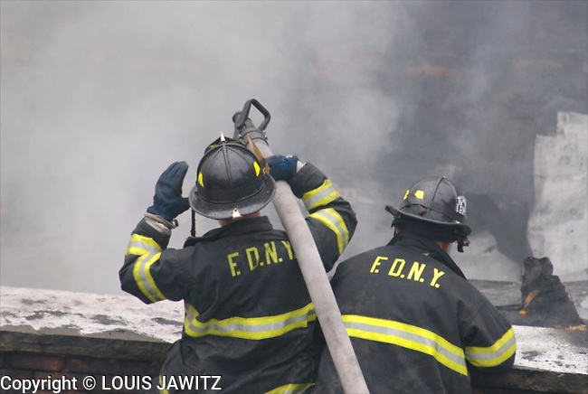 firemen putting out roof fire NYC smoke water flames