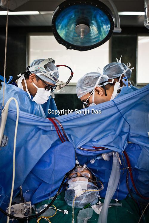 58 year old heart surgeon, Dr. Devi Prasad Shetty and his colleagues conduct an open heart surgery on Ajay Singh Goyal (23) at the Narayana Hrudayalaya in Bangalore, Karnataka, India. Photo: Sanjit Das/Panos