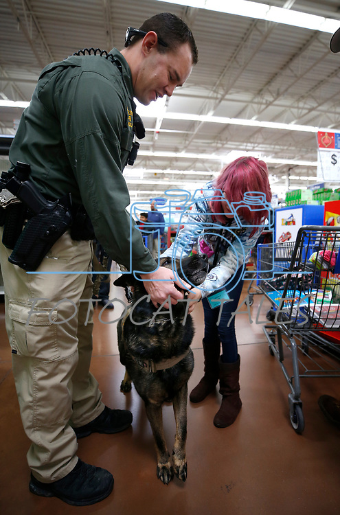 Carson City Sheriff's Deputy Brett Bindley and his K-9 Ivo talk with Sheyann, 12 during the 15th annual Holiday with a Hero program at Walmart in Carson City, on Wednesday, Dec. 19, 2018. The program pairs 240 K-8 students from the Carson City School District&rsquo;s McKinney-Vento program with first responders for a $100 Christmas shopping spree.<br /> Photo by Cathleen Allison/Nevada Momentum