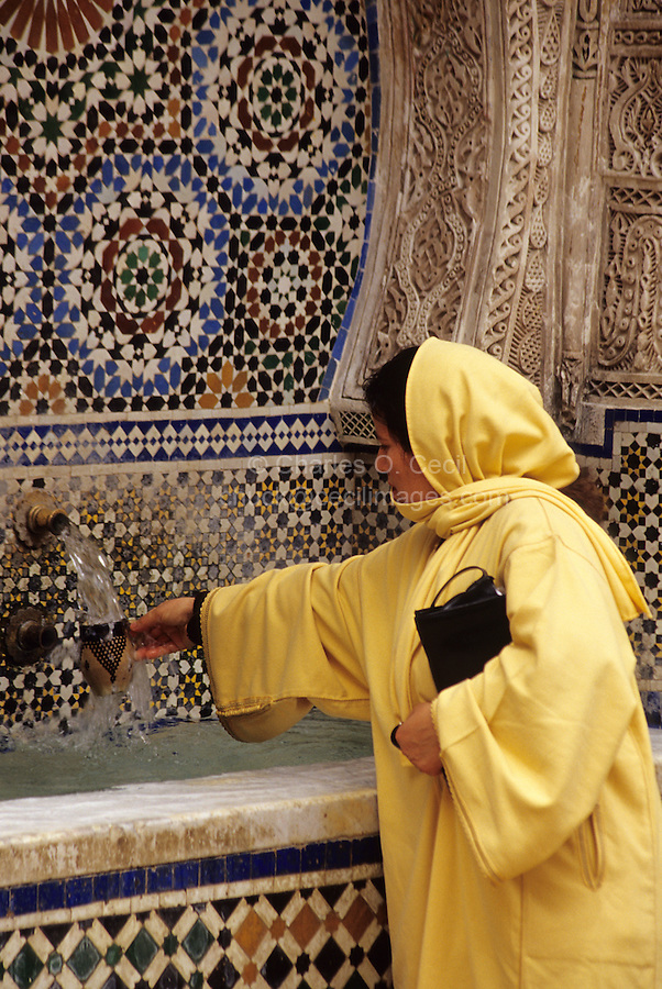 Fez, Morocco - Woman Using Public Cup to Get a Drink of Water at the Nejjarine Fountain in the Old City of Fez.