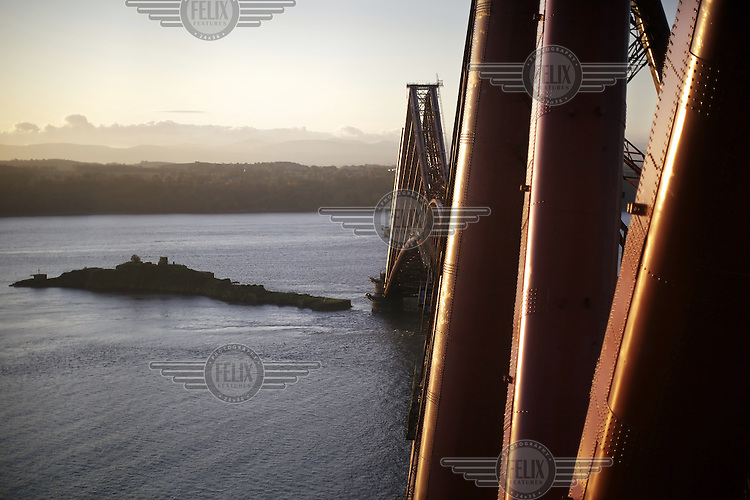 A view of the 125 year old Forth Rail Bridge which spans the river Forth near Edinburgh. The Royal Society for the Protection of Birds (RSPB) protected island of Inchgarvie is visible in the background. Network Rail, the operator of the rail track that leads over the bridge, has spent 10 years and GBP 130 million repainting the 230,000 square metres of steel and 6.5 million rivets on the bridge. The iconic red paint used on the bridge is made to match the red-oxide paint used over 100 years ago. The bridge will now need no further painting for at least 20 years. ...