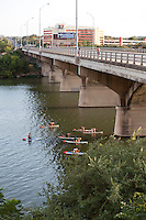 Yoga paddle boarding becomes new fitness craze as as small group of practicers strike zen-like poses while maintaing their balance on a paddle board, Austin, Texas