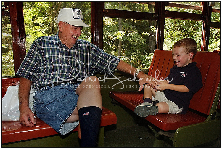 A grandfather tickles his grandson to make him laugh while riding on a trolly car. Model released image can be used to illustrate many purposes.