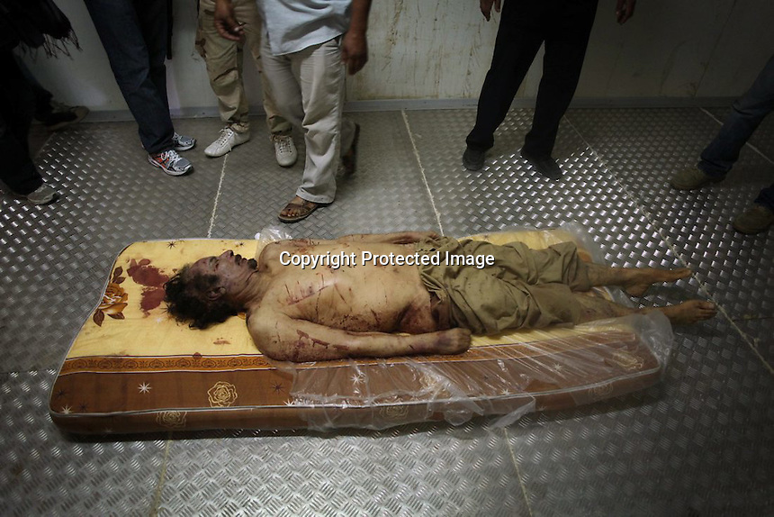 """The body of Libyan dictator Moammar Gadhafi lies on a mattress in a commercial freezer at a shopping center in Misrata, Libya, Friday, Oct. 21, 2011. """"Gadhafi"""""""