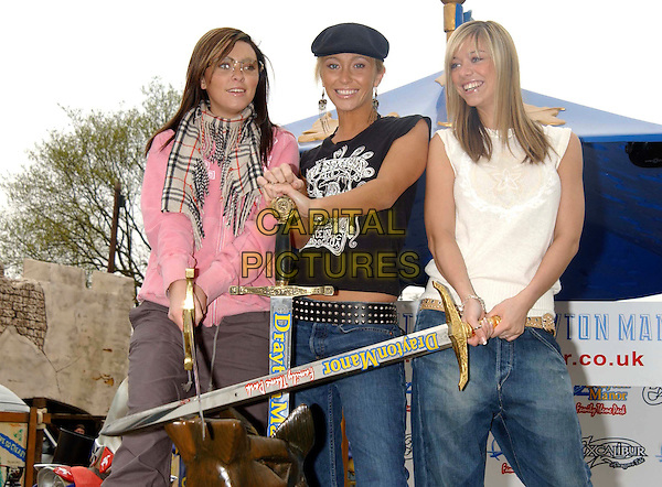 "ATOMIC KITTEN - NATASHA HAMILTON,  JENNY FROST, LIZ McCLARNON.launch new family adventure ride ""Excalibur-A Dragon's Tale"" at Drayton Manor Theme Park.April 24th, 2003.half length jeans denim white black pink burberry scarf hat sword.CAP/PL.©Capital Pictures"
