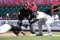 Akron RubberDucks first baseman Bryan LaHair (16) takes a throw as Marcus Lemon (39) dives back to first with John Libka umpire looking on during a game against the Erie SeaWolves on May 18, 2014 at Jerry Uht Park in Erie, Pennsylvania.  Akron defeated Erie 2-1.  (Mike Janes/Four Seam Images)