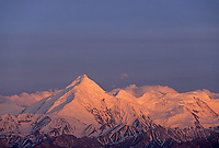 Pink alpenglow on the snow covered mount Brooks of the Alaska Range mountains. Denali National Park, Alaska.