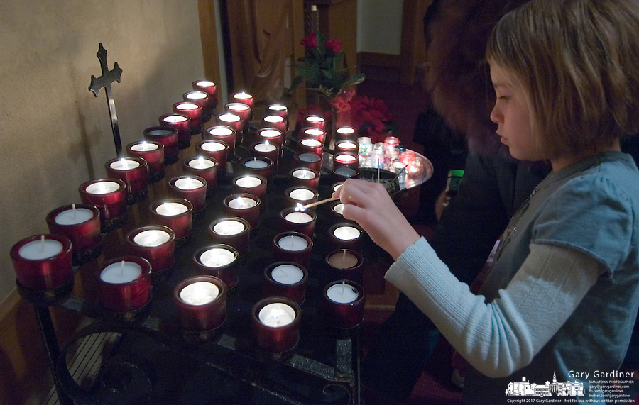 A young girl lights a candle in a Catholic church.