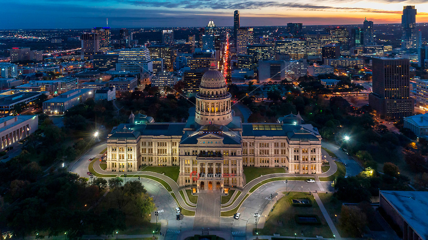 Aerial image of the Texas State Capitol grounds in downtown Austin, Texas with afternoon drive-time traffic on Congress Avenue, the center of Austin's retail and financial district.
