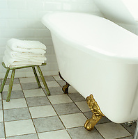 The checked tiles on the bathroom floor contrast with the antique ball-and-claw-foot bath