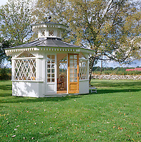 In the garden of a house in the country an elegant gazebo with latticework windows is given pride of place in the centre of the lawn