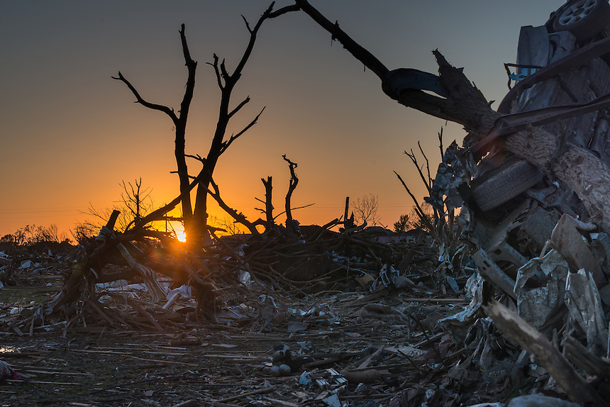 The sun sets over a devastated neighborhood after the passage of a powerful EF-5 tornado in Moore Oklahoma on May 20th, 2013.