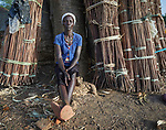 A woman sits among sticks collected for construction use in Bunj, a town in Maban County, South Sudan. Maban is host to four refugee camps that together shelter more than 130,000 refugees from the Blue Nile region of Sudan. Jesuit Refugee Service, with support from Misean Cara, provides educational and psycho-social services to both refugees in the camps and the host community.