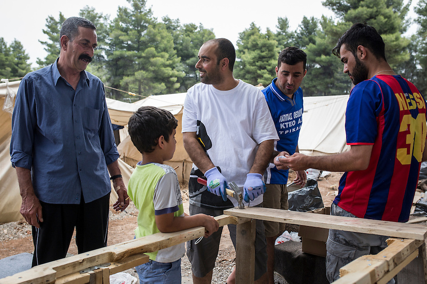 Noh family members including the patriarch, Dijwar, constructing a large table out of pallets and tools donated to them by volunteers at Ritsona Camp. The family are Yazidi and immigrated from Iraq due to the ISIS threat nearby. PHOTO BY JODI HILTON/PULITZER CENTER