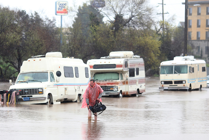 A man who lives in his RV, which was parked in the 300 block of Griffith Street in Salinas, walks through the flooded street on Monday, Feb. 20, 2017.
