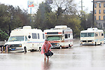 A man who lives in his RV, which was parked in the 300 block of Griffith Street in Salinas, California walks through the flooded street on Monday, Feb. 20, 2017.