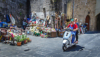Urban Street Photograph of a young couple driving their scooter through the narrow city streets of Rhodes, Greece.
