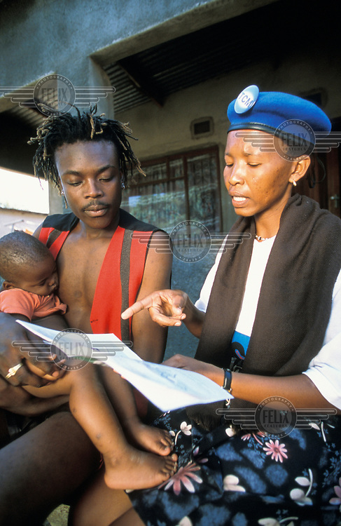 TCM (Total Community Mobilisation) worker with a father and his child. TCM is a Botswanan initiative, providing one field worker for each 2000 members of the community. TCM workers provide support, education and information, especially in regards to health and social issues, and specifically AIDS and HIV.