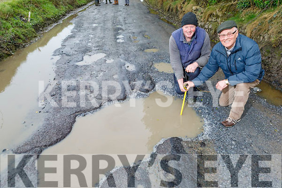 Concerned residents John Reidy and Pat O'Hara examine the deep pot hole in Glandahalin in Ballyheigue on Monday.