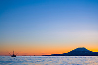 Commercial fishing trolling vessel in Sitka Sound. Sunset behind mount Edgecumbe, an inactive volcano on Kruzof Island, southeast Alaska.