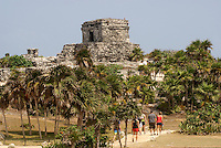 Tourists and Temple of the Wind God at the Mayan ruins of Tulum on the Riviera Maya, Quintana Roo, Mexico.