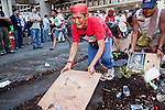Apr. 30 - BANGKOK, THAILAND: A Red Shirt uses one of their home made shields to clean up diesel fuel soaked dirt after they tore down one of their barricades in Bangkok Friday. The Red Shirts moved one of their barricades in the Sala Daeng Intersection in Bangkok Friday In one of the first positive moves to take place since the Red Shirts occupied central Bangkok in early April. The barricade was moved far enough back to open one lane of traffic on  Ratchadamri Street to allow ambulance access to King Chulalongkorn Memorial Hospital, a large hospital at the intersection. Many of the patients in the hospital have been moved to other hospitals because a group of Red Shirts entered the hospital Thursday looking for Thai security personnel, who were not in the hospital. The stand off between the Red Shirts and the government enters its third month in May. The Red Shirts continue to call for Thai Prime Minister Abhisit Vejjajiva to step down and dissolve parliament and demand the return of ousted Prime Minister Thaksin Shinawatra.   PHOTO BY JACK KURTZ