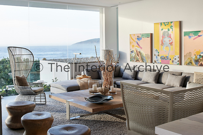 The multi-functional living space embraces the notion of casualness through its relaxed and laid back décor. Objects and accessories are kept to the minimum, such as the carefully chosen pieces displayed on the chunky coffee table, which is assembled from wire-brushed builder's planks. The full height window give access to the spectacular view beyond.