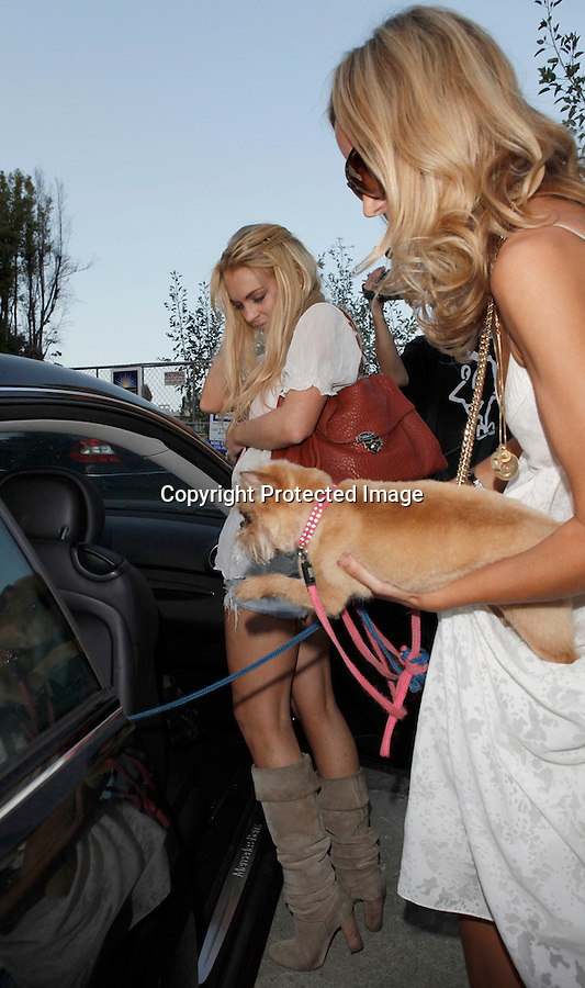 """June 12th 2010..Lindsay Lohan leaving a Hollywood Hills party with her sister Ali &  Lady Victoria Lindsay was drinking a Hangover energy drink. Lindsay seemed pretty happy & was smiling & posing while showing off her new red purse. Ali was carrying a Vogue beach bag & wearing bell bottoms. Lindsay was checking out Lady Victoria's butt as she got into the car.  As Lindsay left the pool party a photographer asked, """"Hey Lindsay did you go swimming?"""" Lindsay replied, """"Ha ha you know I can't swim with a SCRAM bracelet on!"""" ...AbilityFilms@yahoo.com.805-427-3519.www.AbilityFilms.com"""