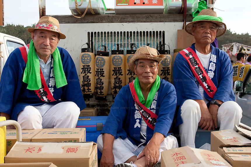 Festival supporters sit in a truck that is carrying saki a during the Hamaorisai Matsuri that takes place on Southern Beach in Chigasaki, near Tokyo, Kanagawa, Japan Monday July 18th 2011. The festivals marks the celebration of Marine Day and the rescuing of a divine image that was washed ashore in the area. Over thirty Mikoshi or portable shrines are carried through the night from surrounding shrines to arrive on the beach for sunrise. There they are blessed and then carried into the surf to purify them.