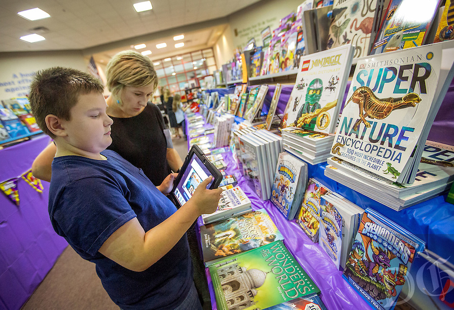 NWA Media/JASON IVESTER --10/02/2014--<br /> Travin (cq) Witham (cq), sixth-grader, and Natalie Young, teacher, look over books for sale on Thursday, Oct. 2, 2014, during a book fair in the library for Old High Middle School and R.E. Baker Elementary School in Bentonville. The book fair continues for the students from both schools today (FRIDAY).