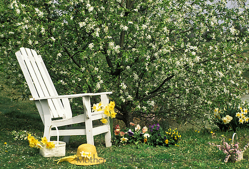 White Adirondack chair beside blooming pear tree is surrounded by baskets and pots of spring flowers and yellow spring hat -- with spring flowers ready for planting