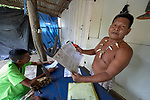 "Sebastian Castillo Gomes holds official papers pertaining to the legal status of the Nacoes Indigenas neighborhood in Manaus, Brazil. The neighborhood is home to members of more than a dozen indigenous groups, many of whose members have migrated to the city in recent years from their homes in the Amazon forest. <br /> <br /> The residents have had to struggle to defend their urban homes. ""We used to fight with bows and arrows,"" sand Castillo Gomes, ""but today we fight with legal papers."""