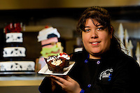 Portrait of Erica Baez-Hortob, food artist and owner of Cloud 9 Confections & Bakery, located inside the 7th Street Public Market in Uptown Charlotte, North Carolina. Building upon the success of Charlotte's Center City Green Market, the Seventh Street Public Market opened in 2012 to be a year-round market serving and celebrating local food artisans, entrepreneurs and local and regional farmers. Image is part of a series of photos taken of the Center City attraction.