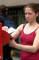 Montreal (Qc) CANADA -file - Model Releasd illustration  photo -<br /> <br /> A young woman mail a letter in a Canada Post Mailbox outdoor.<br /> <br /> <br /> <br /> photo : Pierre Roussel /  Images Distribution