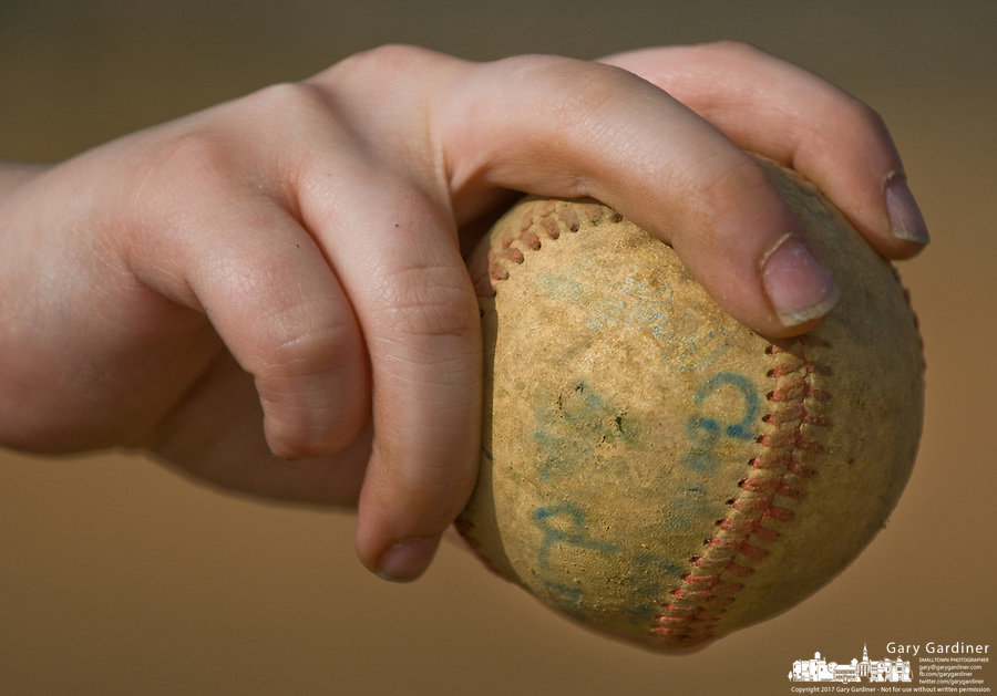 Boy shows how he holds the ball as a baseball pitcher