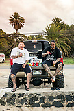 USA, Oahu, Hawaii, Daytyn Ragragola and Kenneth Meyer Jr. sit on the back of an enormous pickup truck on the North Shore at Haliewa Beach Park
