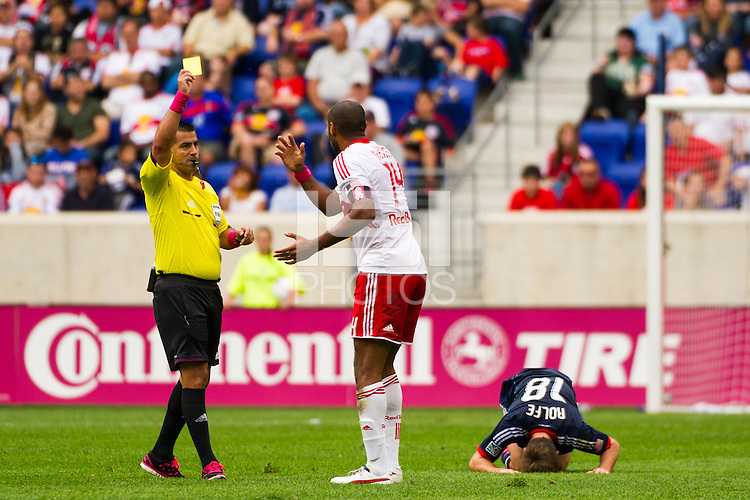 Referee Ricardo Salazar gives a yellow card to Thierry Henry (14) of the New York Red Bulls for a foul on Chris Rolfe (18) of the Chicago Fire. The Chicago Fire defeated the New York Red Bulls 2-0 during a Major League Soccer (MLS) match at Red Bull Arena in Harrison, NJ, on October 06, 2012.