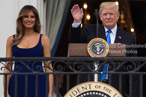 United States President Donald J. Trump delivers remarks as first lady Melania Trump looks on from the Truman Balcony on July 4, 2017, in Washington, DC. The president was hosting a picnic for military families for the Independence Day holiday.  <br /> Credit: Zach Gibson / Pool via CNP