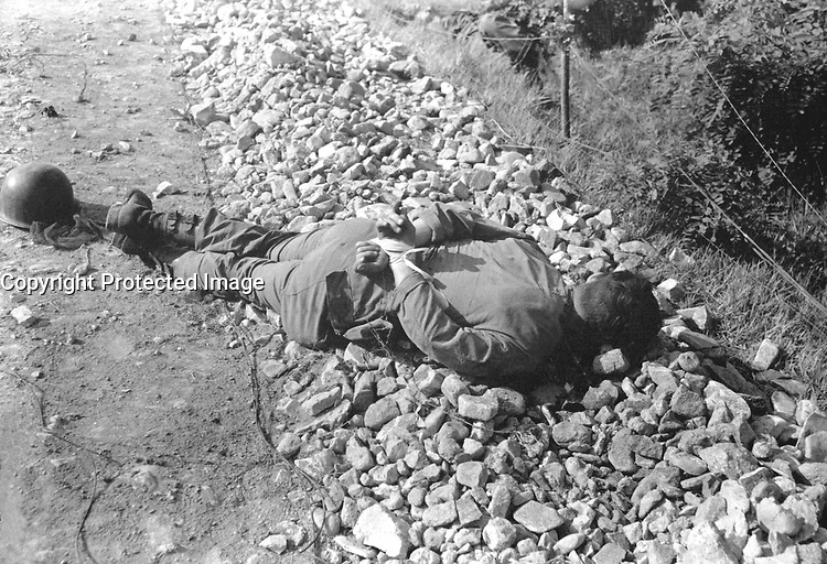 One of four Americans of the 21st Inf. Regt. found between the forward observation post and the front line.  The men were probably captured the night of July 9th, and shot thru the head with their hands tied behind their backs.  July 10. 1950.  Cpl. Robert Dangel. (Army)<br /> NARA FILE #:  111-SC-343302<br /> WAR &amp; CONFLICT BOOK #:  1510
