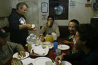 "10/20/03 crab NWS::  Steve Toomey, part owner of the F/V Exito (standing left), shares breakfast and a laugh with the crew during a break in the galley during the Bristol Bay red king crab season.  Either Toomey, who usually takes care of cooking while fishing, or the other captain, Quinn Ferguson, will eat with the crew during meals to try and keep them as informed as possible as to what the next plan is or ""when their next 15 minutes of sleep will be."""