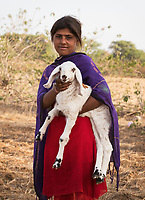 girl carrying goat