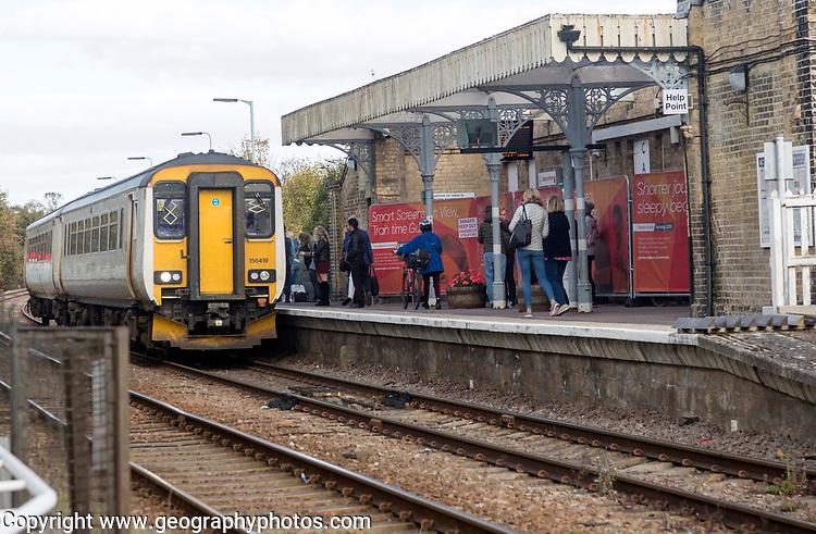 Passengers on platform train arriving, railway station, Saxmundham, Suffolk, England, UK British Rail Class 156 Super Sprinter diesel multiple unit  Greater Anglia train