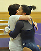 Jessica Lopez of Plainview JFK gets a congratulatory hug from coach Debbie Rut after scoring a 9.1 on the uneven bars in a Nassau County varsity gymnastics meet against Massapequa at McKenna Elementary School on Monday, Feb. 1, 2016. Plainview JFK won the meet by a score of 164.7-163.6.