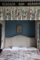 An 18th century chintz hangs from the ornately carved four-poster bed in a bedroom at Tullynally