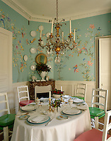An intricate floral wallpaper adorns the walls of this elegant dining room designed in 18th-century style
