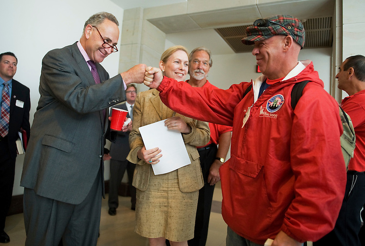 "UNITED STATES - JULY 20:  John Feal, right, a former construction worker and first responder to ground zero on 9/11, gets a fist bump from Sen. Charles Schumer, D-N.Y., as Sen. Kirsten Gillibrand, D-N.Y., looks on, before a news conference to call for passage of legislation to ""provide first responders and public safety officials with critical interoperable radio airwaves needed to effectively communicate in the event a major response is needed.""  (Photo By Tom Williams/Roll Call)"