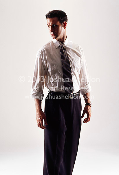 Caucasian looking man wearing a white shirt and tie looking sideways
