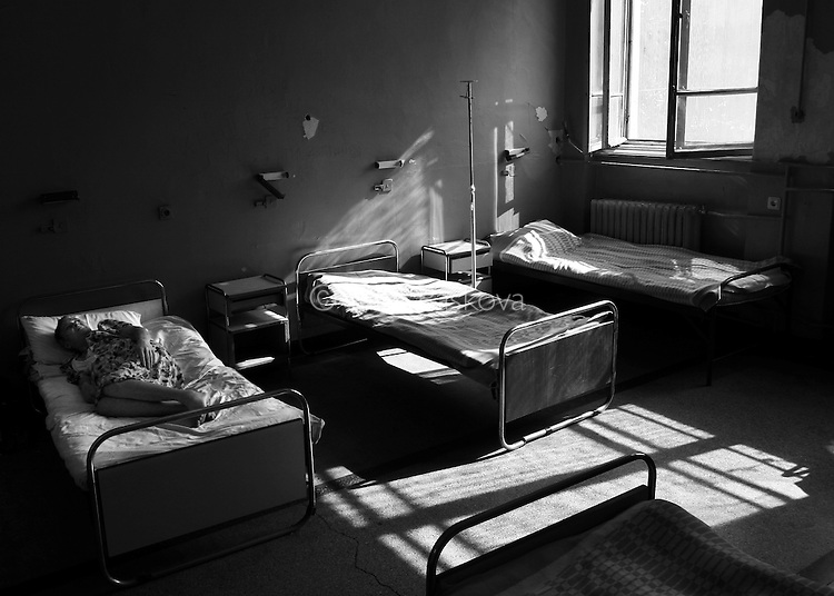 A female patient stares at the ceiling while laying in bed for an afternoon nap in the psychiatry ward of a county hospital in Bulgaria on August 16, 2007.